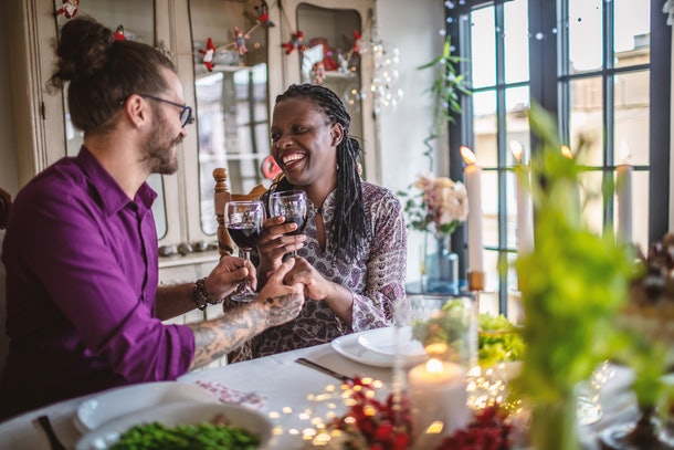 A happy couple clinks their wine glasses while enjoying a romantic and festive dinner at home.