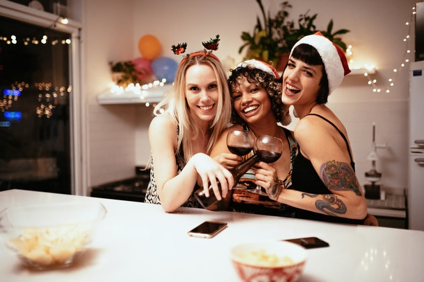 Three friends clink wine glasses and beer bottles together while celebrating Christmas in their home.