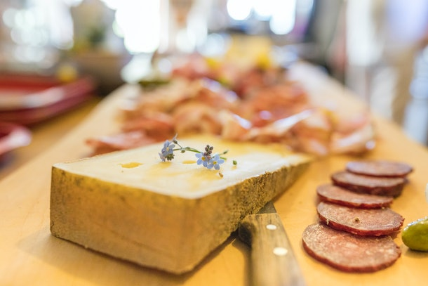 Some cheese and meat sit on a charcuterie board in a kitchen.