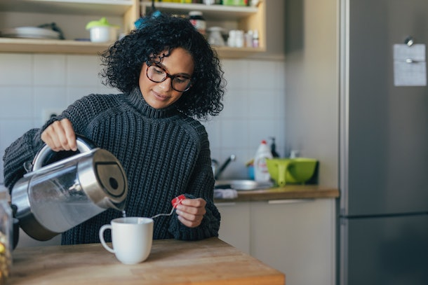 A woman with a gray sweater on pours herself tea in her kitchen.