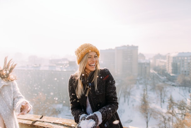 A happy blonde woman laughs while getting ready to throw a snowflake on a sunny day.