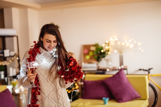 A woman is festive and cozy at home with fairy lights and a red garland draped around her neck, while holding a glass of champagne.