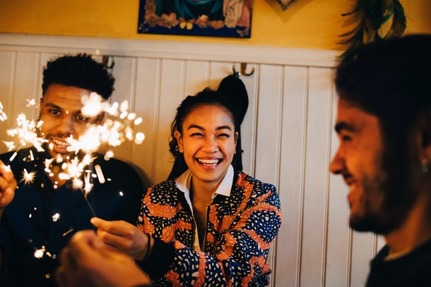 A young woman smiles while wearing a fashionable coat and holding a sparkler on a throwback New Year's Eve.
