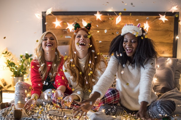 Three happy friends toss glitter in the air in a bedroom while celebrating the holidays.