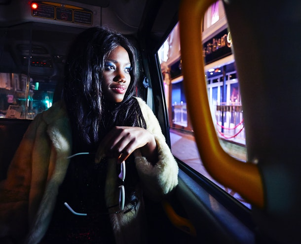 A young Black woman looks out a car window while driving by neon lights.