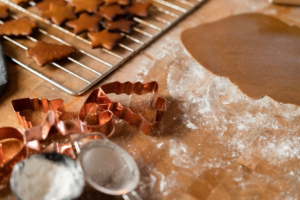 Copper cookie cutters sit on a table that's covered with flour and gingerbread dough.