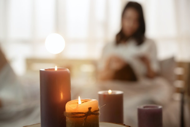A woman relaxes in her home by her candles.