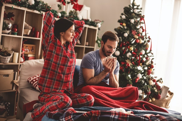 A happy couple enjoys their cozy Christmas home while in festive PJs.