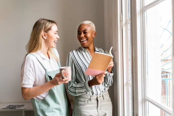 Two women laugh in a sunny room while holding a new journal.