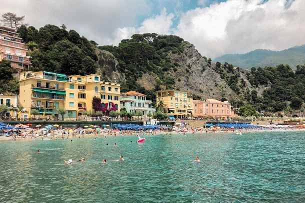 The pastel buildings of Monterosso al Mare sit in the Italian cliffside on a busy afternoon.
