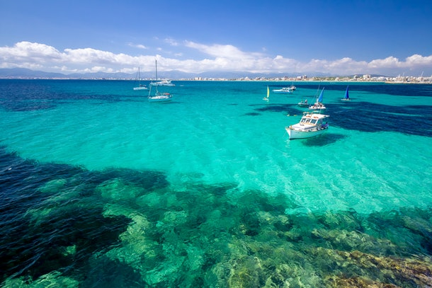 Boats sit in the teal waters off the coast of Mallorca, Spain on a sunny day.