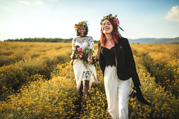 A lesbian couple takes pictures in a flower field at golden hour after getting married.