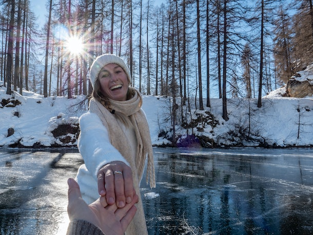 A happy women wearing a scarf, sweater, and beanie skates on an icy pond while holding her partner's hand.