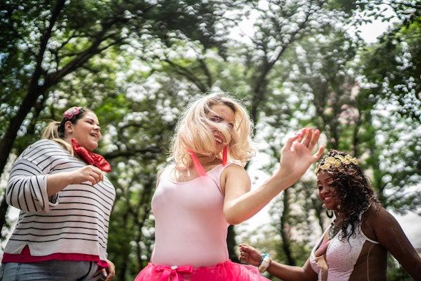 Three friends dance amongst trees in celebration of Mardi Gras.