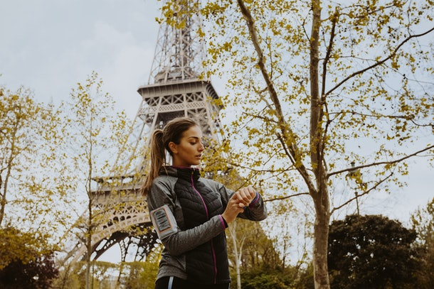 A woman in workout apparel looks at her watch with the Eiffel Tower in the background.