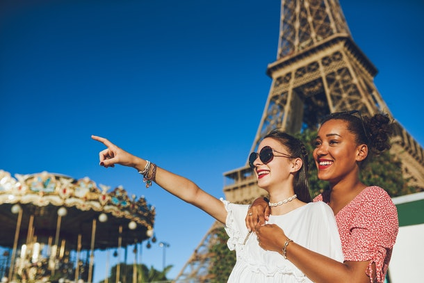 Two friends smile near the Eiffel Tower in Paris on a sunny day.
