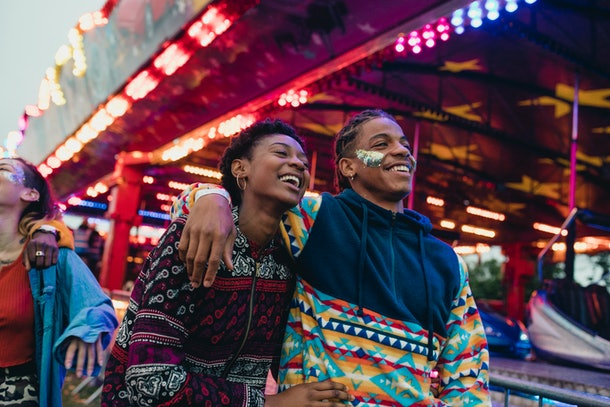 A couple walks through neon lights and arcade games during a birthday celebration.