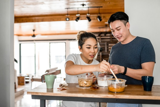 A couple sits at the counter in their kitchen and splits containers of food.