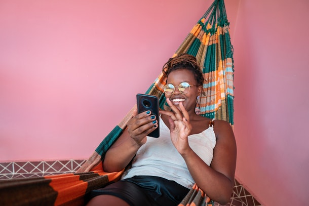 A young woman relaxes in a hammock surrounded by a pink wall while writing a belated birthday message on her phone.