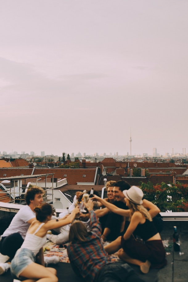 A group of friends celebrates a birthday while on a rooftop in the city.