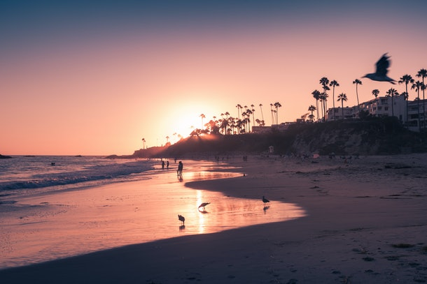 A sunset in Laguna Beach, California turns the sky vibrant shades of pink and purple.