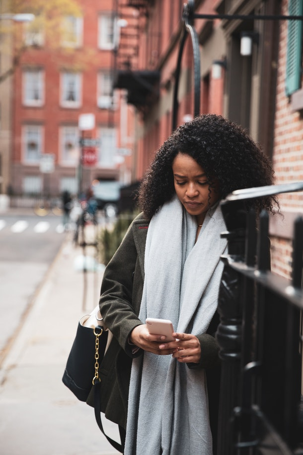 A young woman quietly looks at her phone while leaning against a brick building in the city.