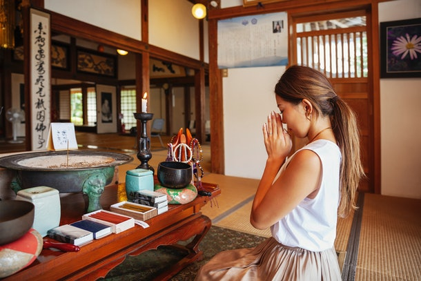 A young woman prays in a temple in Japan.