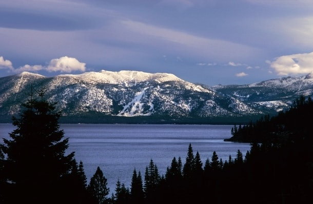 The mountains of Lake Tahoe, California are covered with snow in the winter.