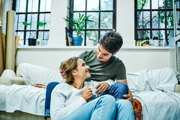 A young couple cuddles up with a cup of tea in their apartment.