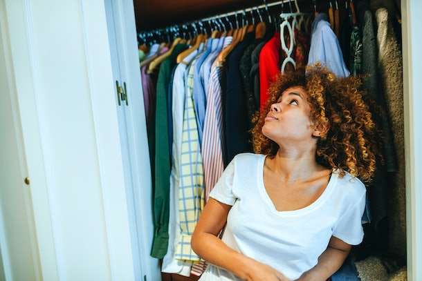 A woman looks up at her freshly-organized closet.