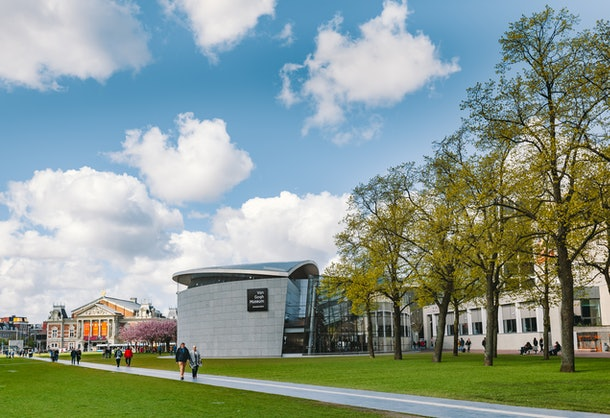 Visitors walk around the Van Gogh Museum in Amsterdam on a cloudy day.