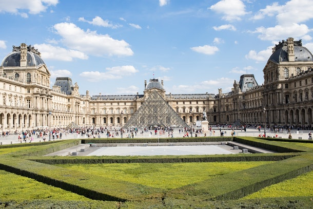 The Louvre in Paris is fairly crowded on a sunny day in the summer.