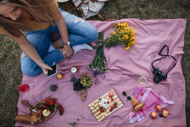 A young woman sits on a pink blanket in her backyard and has a picnic.