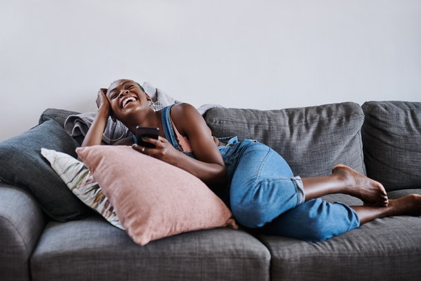 A young woman laughs while lounging on the couch and playing on her phone.