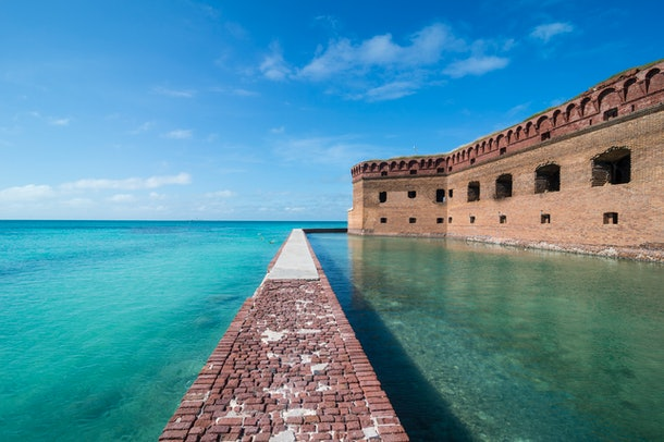 Dry Tortugas National Park in Florida features teal waters, coral reefs, and a brick walkway.