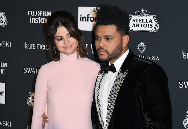 The Weekend wraps his arm around Selena Gomez on the red carpet.