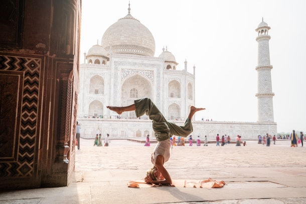 A young woman does a headstand while visiting the Taj Mahal.