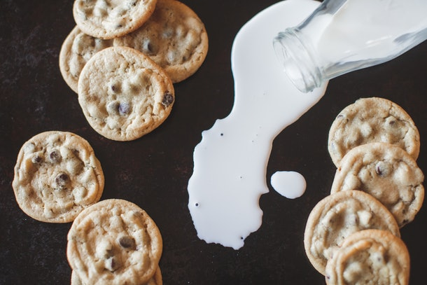 Homemade chocolate chip cookies sit on a table with spilled milk.