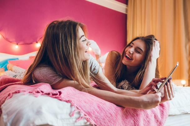 Two friends laugh while laying on a pink bed while one holds up an iPad.
