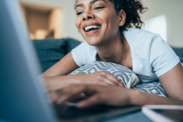 A young woman laughs while laying on her couch and video chatting on her laptop.