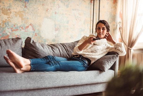 A young woman lays on a couch and watches a movie on her television.
