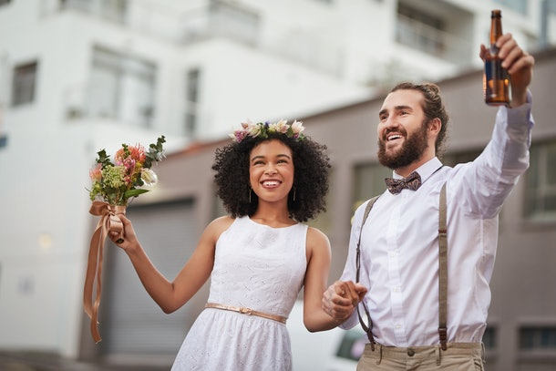 A young couple poses for a wedding photo in the city while holding a bouquet and bottle of beer.