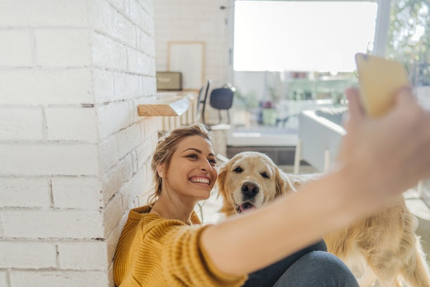A young woman in a yellow sweater takes a selfie with her golden retriever.
