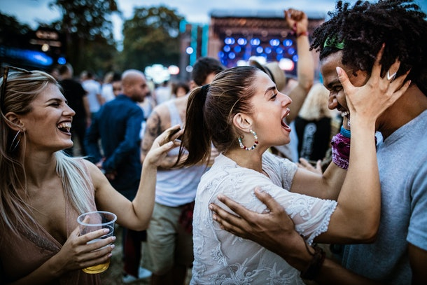 A young couple embraces and sings while at a music festival.
