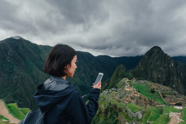 A young woman stands in front of Machu Picchu with her phone in her hand.