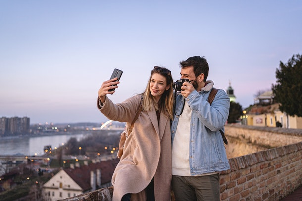A young couple takes a selfie while traveling and exploring at sunset.