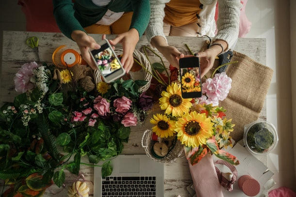 Two women sit at a table with bouquets of different flowers and a laptop.
