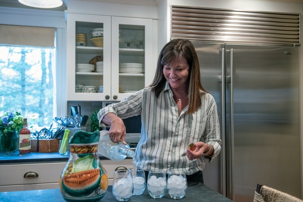 A happy woman pours vodka into a glass while making Bloody Marys in her kitchen.