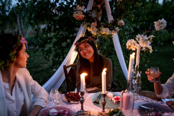Three friends with flower crowns sit at a beautifully decorated table outside for dinner.