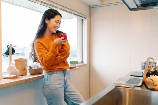 A young woman stands in her kitchen with a red mug while on video chat.